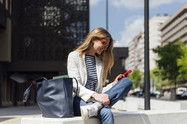Smiling blonde business woman looking at her mobile phone