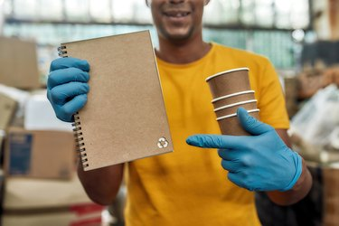 Notebook produced from recycled cups held by man