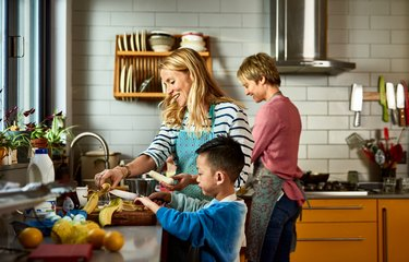 couple cooking with son in kitchen