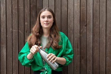 A girl holds a stainless steel reusable water bottle