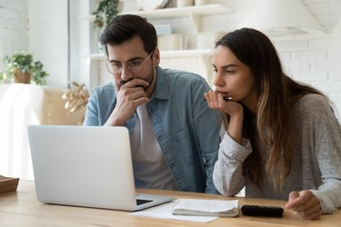 Couple with calculator and papers looking at computer screen.