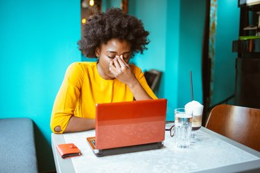 Tired and worried young African-American woman working on a laptop