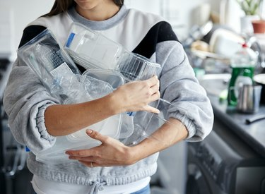 Woman holding armful of used plastic containers in kitchen