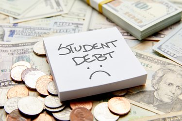 Student debt with sad face written on white sticky note on top of cash money with stack of money and coins