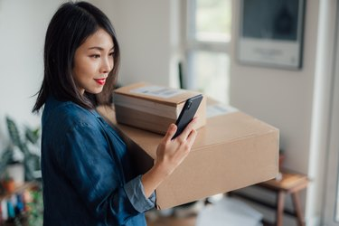 Young woman reading message on mobile phone whilst carrying a stack of delivery boxes at home
