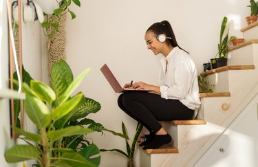 Happy young latin woman enjoying studying remotely from home