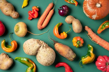 Trendy ugly organic vegetables. Assortment of fresh eggplant, onion, carrot, zucchini, potatoes, pumpkin, pepper in craft paper bag over green background. Top view. Cooking ugly food concept. Non gmo vegetables