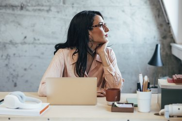Beautiful Businesswoman Sitting at Her Desk in the Office and Daydreaming