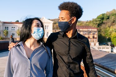 Portrait of a young couple walking down the street embracing a happy blue sky on Valentine's Day with a face mask due to the 2020 covid-19 coronavirus pandemic