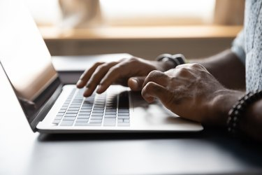 Close up African American male hands typing on laptop keyboard
