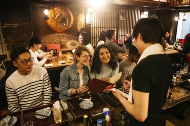 Waiter taking food order from young women in Izakaya