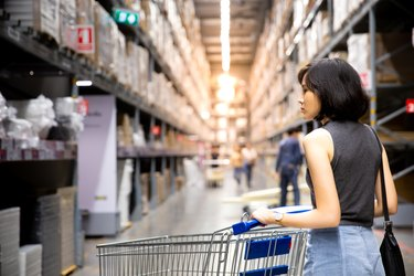 An asian woman doing shopping  and walking with her cart in cargo or warehouse.