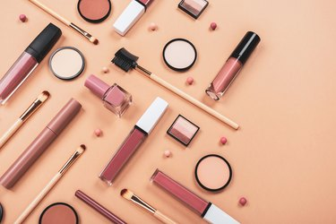 Set of different makeup accessories on beige, brown background. Knolling concept. Cosmetic products for skin care. Eyeshadow, blush, face powder, nail polish, brushes and lipstick.