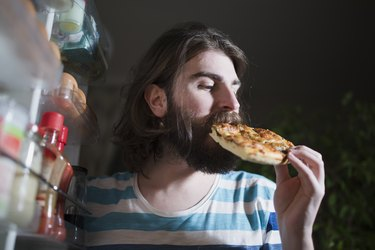Young man eating pizza slice in front of the refrigerator