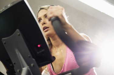 Mixed Race woman riding stationary bicycle