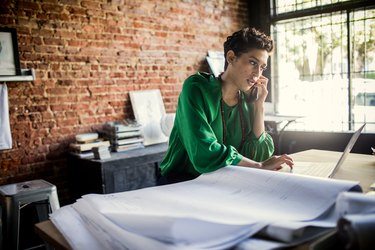 Businesswoman looking over architecture blueprints in office