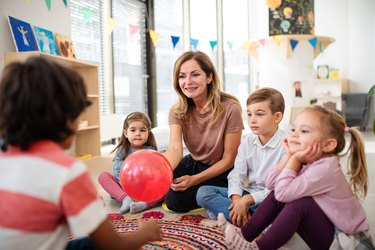 Pre- school teacher sitting on floor and playing with children indoors in nursery.