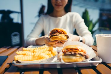 Asian woman enjoying freshly made delicious burger with fries.