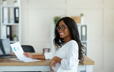 Beautiful black business lady working with documents at her desk in modern office, panorama