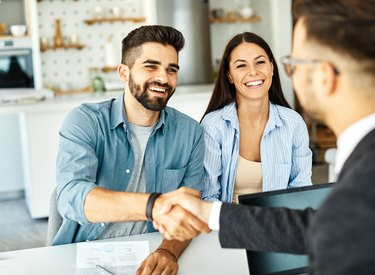 young couple shaking hands deal contract real estate investment business agreement agent handshake signing