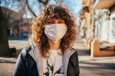 Happy young woman wearing facial mask for virus protection