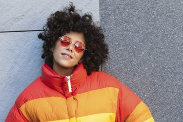 Young woman wearing sunglasses smiling while leaning on wall