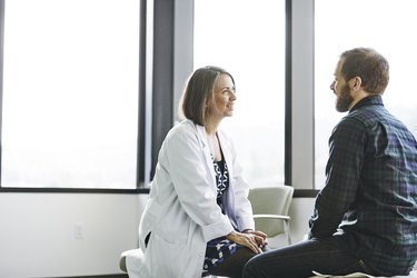 Female doctor in discussion with male patient in exam room