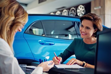 Car dealer sales car to the customer and they are signing the contract