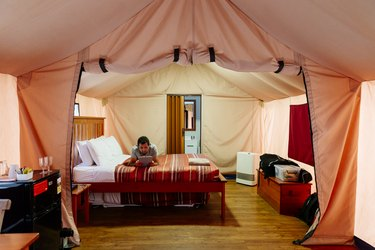 A man laying on a bed reading, inside of a 'glamping' tent