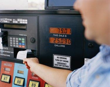 Man getting receipt from gas pump