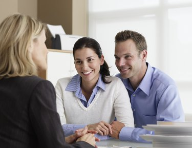 Mid adult couple talking with insurance agent in office, smiling