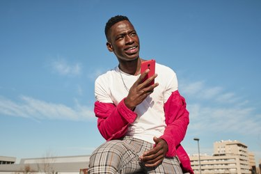Young man in red jacket looking at smart phone outdoors