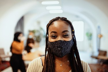 African-American businesswoman working in office after reopening, wearing face mask to prevent covid-19 spreading in office
