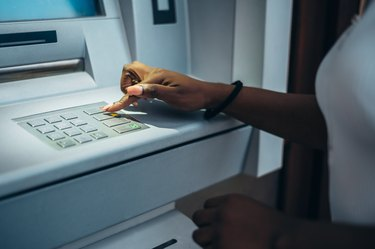 African american woman typing pin code and withdrawing cash at the ATM