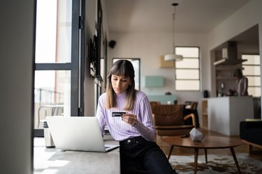 Young woman doing online shopping using credit card at home