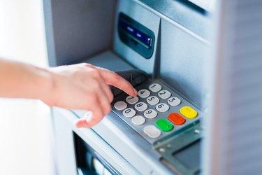 Closeup of hand entering PIN code into an ATM bank machine.