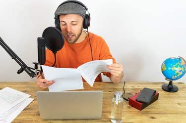 Busy man recording podcast about traveling at table with microphone