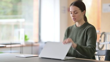 Young Woman Closing Laptop and Leaving