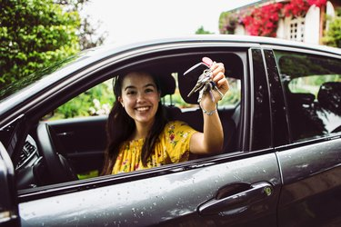cheerful young woman showing the keys of her new car
