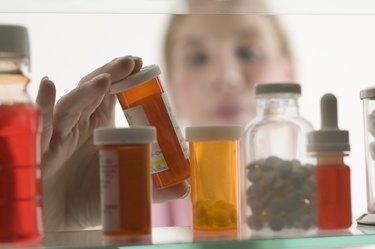 Person grabbing bottle of medicine