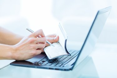Persons hands writing a personal bank cheque using a pen while working on a laptop computer.