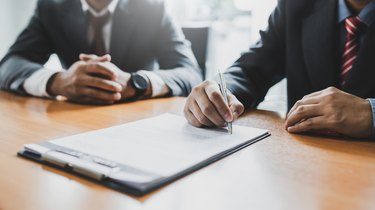 Business people sign investment agreements to buy and sell business.