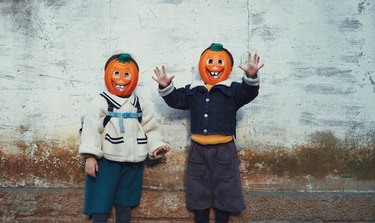 Portrait Of Smiling Boy Standing Against Wall During Halloween