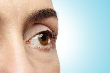 Close-up of female eye on blue background.