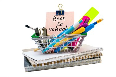 A shopping cart with office supplies on exercise books and words back to school on paper sticky sheets. Purchases for study, education concept on white background. Mini basket with stationery.