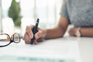 Closeup shot of an unrecognisable businesswoman going through paperwork in an office
