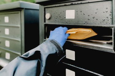 Woman Retrieves Package Wearing Protective Gloves