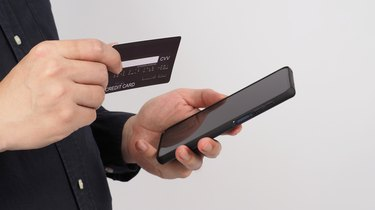 Hand is holding smart phone and black credit card on white background.
