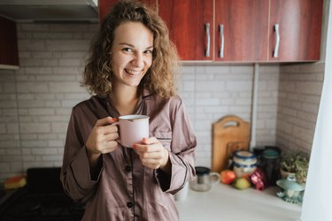 A young beautiful woman drinks a tea or coffee in the domestic kitchen in the morning