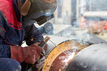 Construction worker arc welding the metal pipe.